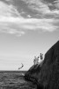 Photograph of teens cliff diving on Aproador point in Rio de Janeiro, Brasil.