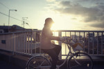 Photograph of an elderly woman riding a bicycle over a canal bridge near Machida, Japan.