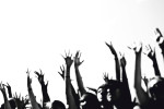 Black and white photograph of the raised hands of excited fans at the Van' Warped Tour in Houston, Texas.