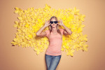 Photographic portrait of a young girl with sunglasses on in front of a wall of hand-made yellow paper flowers.
