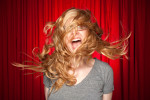 Photographic portrait of a blond girl screaming in front of a bright red curtain.
