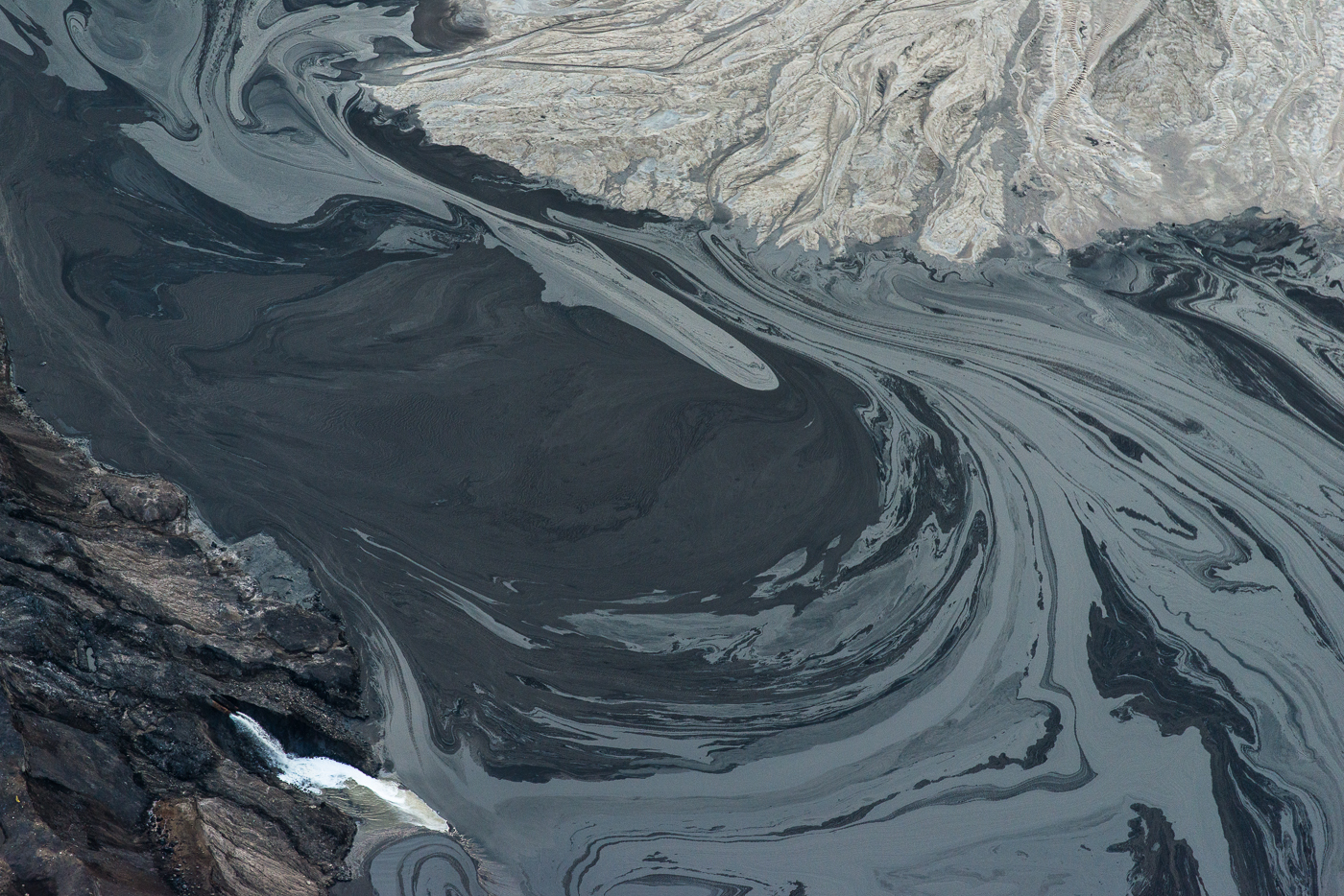 Effluent pipe and tailings pond. Alberta tar sands.