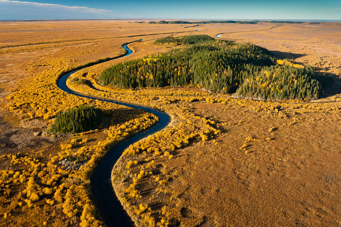 A tributary of the Slave River winds its way through the vast Athabasca Delta, the world's largest freshwater delta. A {quote}Ramsar{quote} designated site of international importance, both the toxic impact of the Tar Sands, as well as the vast amounts of water drawn from the Athabasca River which flows into it, threaten its ecological integrity.