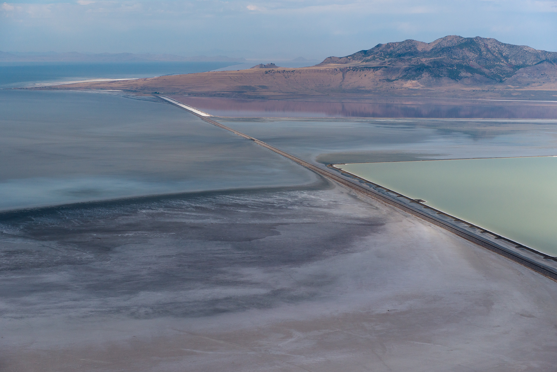 Salt Lake Evaporation Pond #1. Great Salt Lake Utah, USA 2012.  Salt evaporation pond clusters adjacent to Great Salt Lake in Utah. Water from the Great Salt Lake is pumped into the desert flats that border the lake and when this water evaporates, salt, potassium, calcium and other minerals, are left behind. The colors of the ponds result from both the variations in salinity and from the algae content. While these operations are not polluting in themselves, there are concerns around both the amount of water withdrawn from the lake as well as potential loss of habitat for shorebirds.        Nikon D800E, Nikkor 24-70mm at 70mm.  ISO 800, 1/3200 at f5.