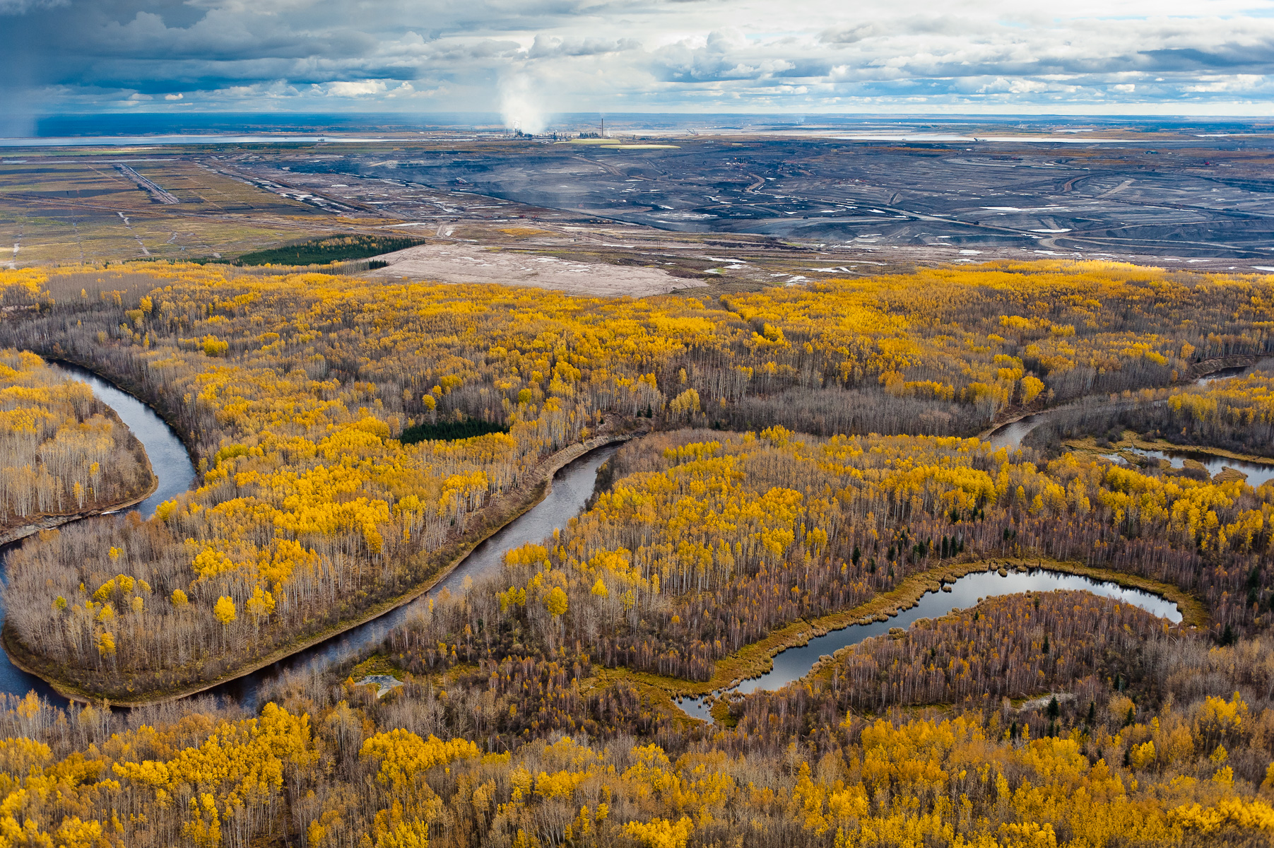 MacKay River, Boreal Forest, and Tar Mine                          Northern Alberta. Canada. 2010.  The boreal forests and wetlands that surround the Tar Sands are the most carbon rich terrestrial ecosystem on the planet, holding almost twice as much carbon as tropical rainforests. Referred to by the tar sands industry as {quote}overburden,{quote} these forests are scraped off and the wetlands dredged, to be replaced by tar mines like this. Exhibition print:  30{quote}x45{quote} archival pigment print on Hahnemuhle bamboo, bonded to aluminum.