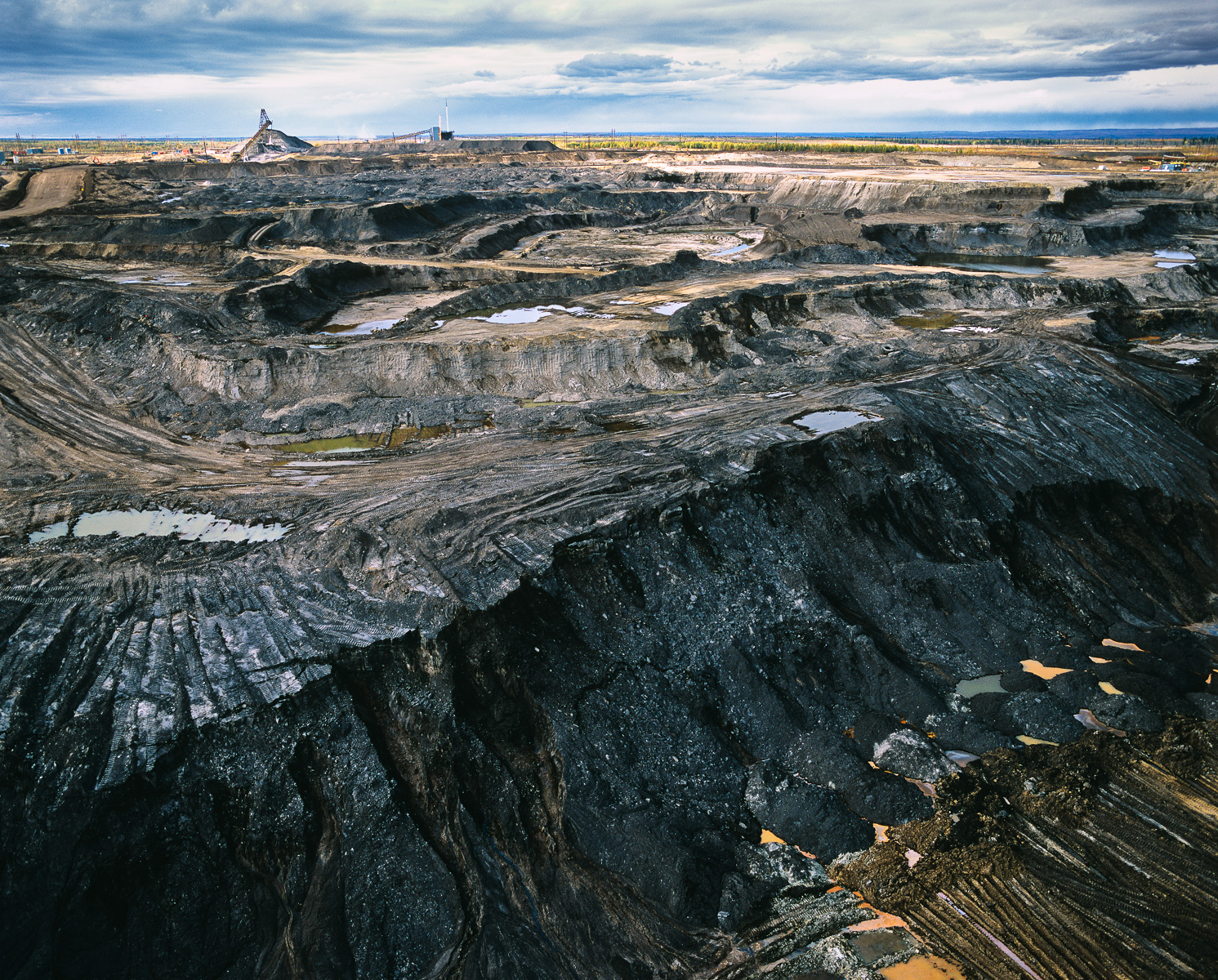 Tar Sands pit mining is done in benches or steps. These benches are each approximately 12-15 meters high. Giant shovels dig the tar sand and place it into heavy hauler trucks that range in size from 240 tons to the largest trucks, which have a 400-ton capacity.