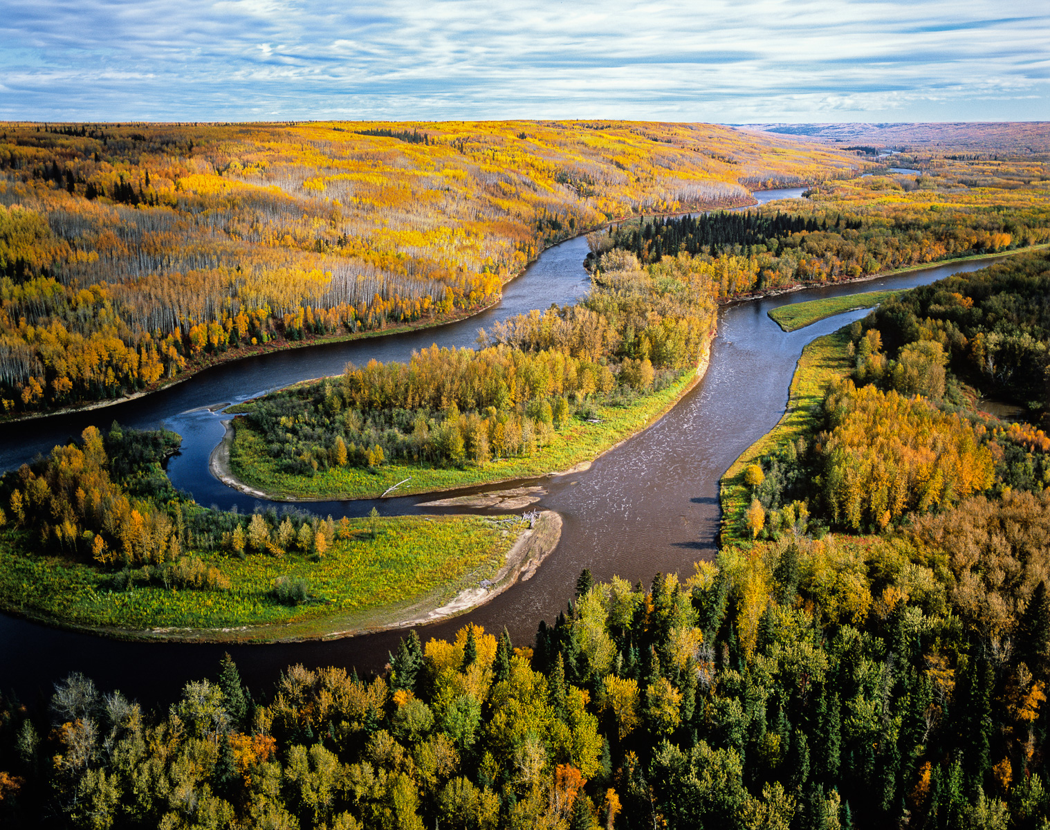 Located just east of Fort McMurray, Alberta, the intact Clearwater River shown here, soon joins the Athabasca River as it winds its way north through the Tar Sands, bordered by the vast, unlined, leaching tailings ponds which border it on either side. Forests like this are tranformed into tar mines to access the {quote}bitumen{quote} buried under them.