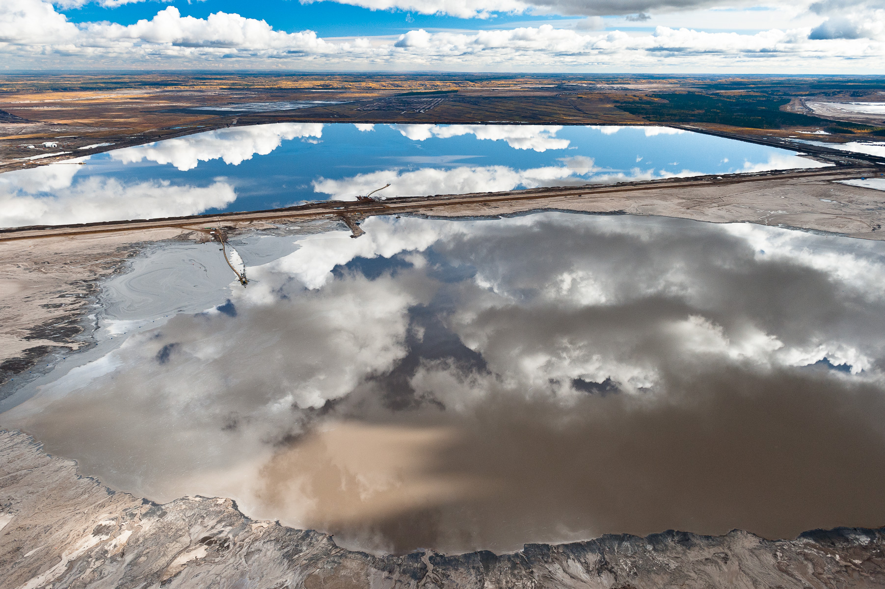 Reflected Sky in Tailings Pond.                                Northern Alberta. Canada. 2010. Disguised by the beauty of a reflection, these toxic tailings ponds are a considerable health risk. These vast toxic lakes are completely unlined and nearly a dozen of them lie on either side of the Athabasca River. Individual ponds can range in size up to 8,850 acres.      Nikon D3 70-200mm f2.8 shot at 190mm, ISO 800, 1/1600 at f4.5  gAlberta Tar Sands, Northern Alberta, Canada.
