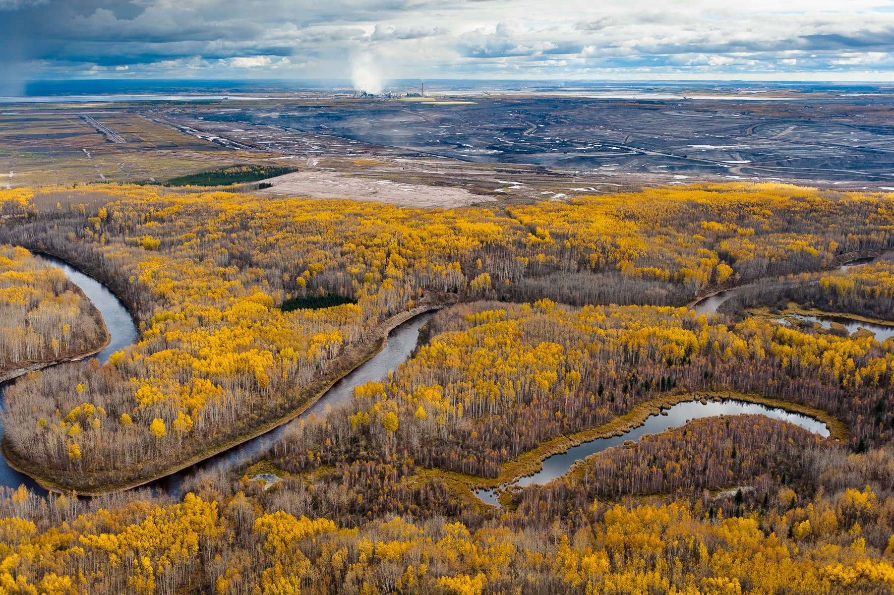 MacKay River, Boreal Forest, and Tar Mine                                                      Northern Alberta. Canada. 2010.  The Boreal Forests and wetlands that surround the Tar Sands are the most carbon rich terrestrial ecosystem on the planet, holding almost twice as much carbon per acre as tropical rainforests. Referred to by the Tar Sands industry as {quote}overburden,{quote} these forests are scraped off and the wetlands dredged, to be replaced by tar mines like this whihc produce significantly more carbon that traditional oil extraction.     Nikon D3, Nikkor 24-70  f2.8. Shot at 34, iso 800, 1/1250 at f4. Alberta Tar Sands, Northern Alberta, Canada.