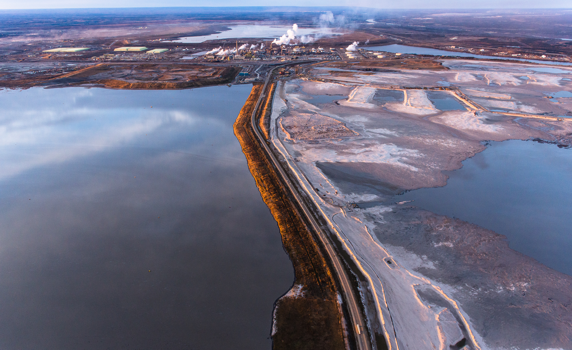 """Syncrude Upgrader, mines, tailings ponds, and Athabasca River. Alberta Oil/Tar Sands, Northern Alberta, Canada. Highway 63, or as it is known to locals as the highway to Hell, cuts through two tailings ponds as head towards an upgrader and into the heart of the Tar Sands.Fine Art Print Price ListOpen and Larger Edition Prints. These are produced to the same high standards as our limited edition prints and offer collectors a more affordable way to get to know our work.Prints  are limited to an edition of 50 in each size above 20"""" X 24"""". Prices are for prints only and do not include tax or shipping.All prices are in US dollars.12""""x18"""" $350.16""""x24""""        $650.20""""x30"""" $1000.24""""x36""""        $1500. 30""""x45"""" $2300.40""""x60""""      $3600"""