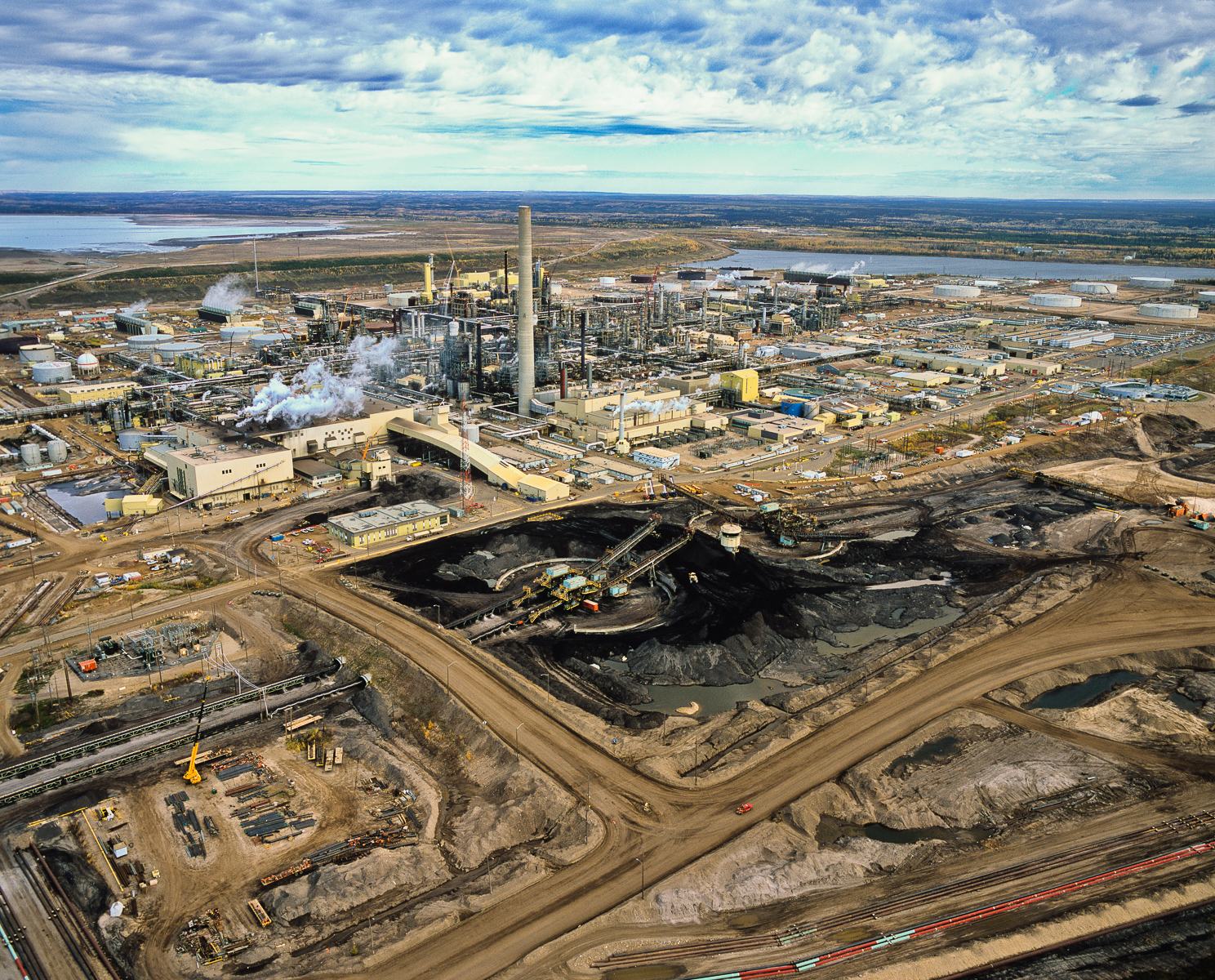 The refining or upgrading of the tarry bitumen which lies under the the boreal forests and wetlands of Northern Alberta consumes more water and energy than conventional oil production and produces more carbon. Each barrel of oil requires 3-5 barrels of fresh water from the neighboring Athabasca River. About 90% of this is returned as toxic tailings into the vast unlined tailings ponds that dot the landscape.