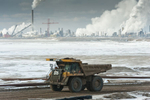 Tar Sands, March 2010. Syncrude frozen tailings pond and Mildred Lake Upgrader in background and dumptrucks. Athabasca Tar Sands, Alberta, Canada.