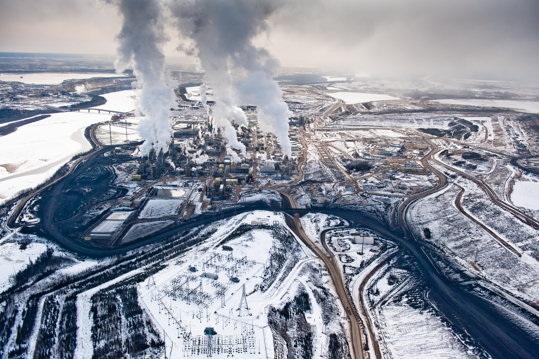 Suncor  Upgrader in Winter                                                                    Northern Alberta. Canada. 2010. The Alberta Tar Sands are Canada's single largest, and fastest growing, source of carbon. They produce about as much carbon annually as the nation of Denmark. The refining of the tar-like bitumen requires far more water and energy than the production of conventional oil and produces significantly more greenhouse gas.     Nikon D3, Nikkor 24-70  f2.8.  Shot at ISO 800, 24mm, 1/8000 at f4.5.  Alberta Tar Sands, Northern Alberta, Canada.