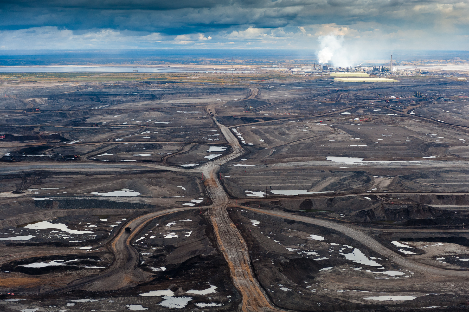 The refining or upgrading of the tarry bitumen which lies under the the boreal forests and wetlands of Northern Alberta consumes more water and energy than conventional oil production and produces more carbon. Each barrel of oil requires 3-5 barrels of fresh water from the neighboring Athabasca River. About 90% of this is returned as toxic tailings into the vast unlined tailings ponds that dot the landscape.g