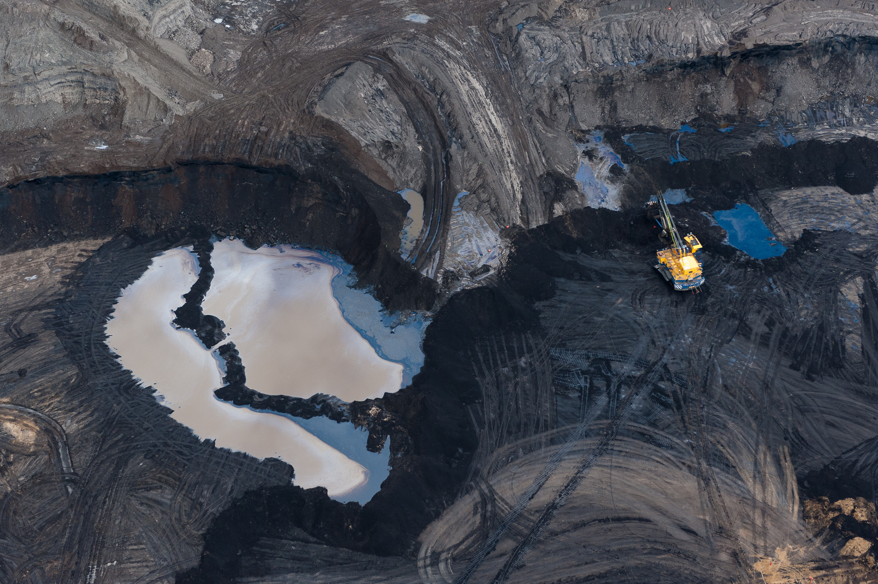 At the edge of an 80-meter deep mine, a massive tar sands machine is dwarfed by the surrounding landscape. The mines, machinery, and trucks of the Alberta Tar Sands were the inspiration for Avatar's Edmonton-born art director's vision of the mining operation on Pandora.
