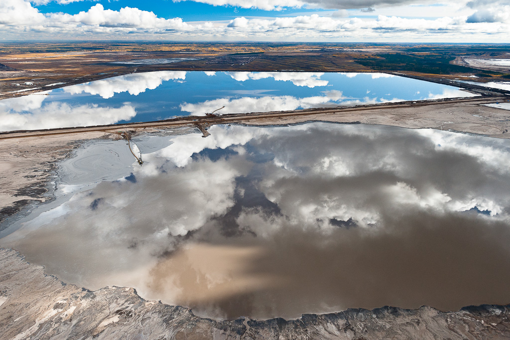 Disguised by the beauty of a reflection, these toxic tailings ponds are a considerable health risk. These vast toxic lakes are completely unlined and nearly a dozen of them lie on either side of the Athabasca River. Individual ponds can range in size up to 8,850 acres.Exhibition print:  40{quote}x60{quote} archival pigment print on Hahnemuhle bamboo, bonded to aluminum.