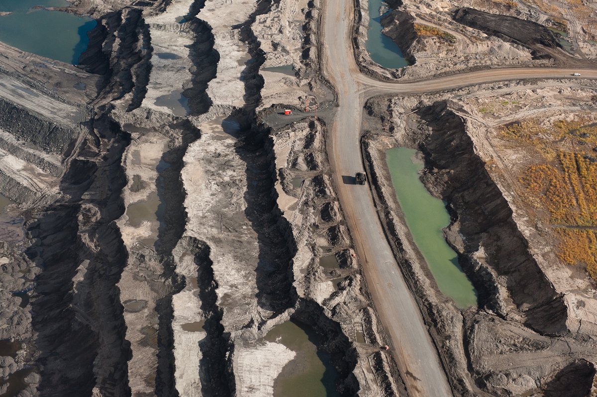 At the edge of an 80 meter deep mine, a massive tar sands truck is dwarfed by the surrounding landscape. These 400 ton trucks are the world's largest measuring 25 feet high, 47 ½ feet long, and 32 feet wide. The mines, machinery, and trucks of the Alberta Tar Sands were the inspiration for Avatar's Edmonton born art director's vision of the mining operation on Pandora. Exhibition print:  30{quote}x45{quote} archival pigmentprint on Hahnemuhle bamboo, bonded to aluminum.