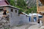 A Kalash woman, left, speaks with a man near the only mosque in Brun, in the Kalash Valley of Bumburet.  The mosque is adjacent to the girls' government school, where teachers are Muslim and female children are encouraged to veil themselves.