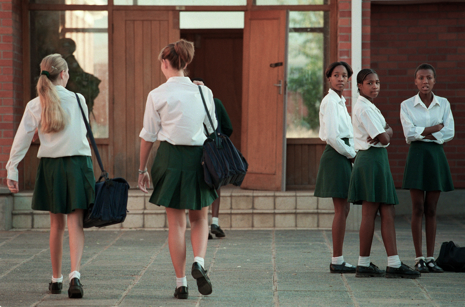 FG.Vryburg.1.0429.ARVryburg High School has been the scene of strong and sometimes violent racial tension between black and white students as well as their parents. Most recently a black student stabbed a white student in the neck with scissors. A group of black students watch as white fellow students arrive for school at Vryburg High School. Photo taken 4/15/99.Photo/Art by:Anacleto Rapping