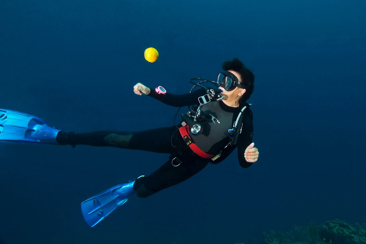 I love incorporating fruit into dive shots.  Here Jaye takes a close look at an orange that is hovering mid-water.