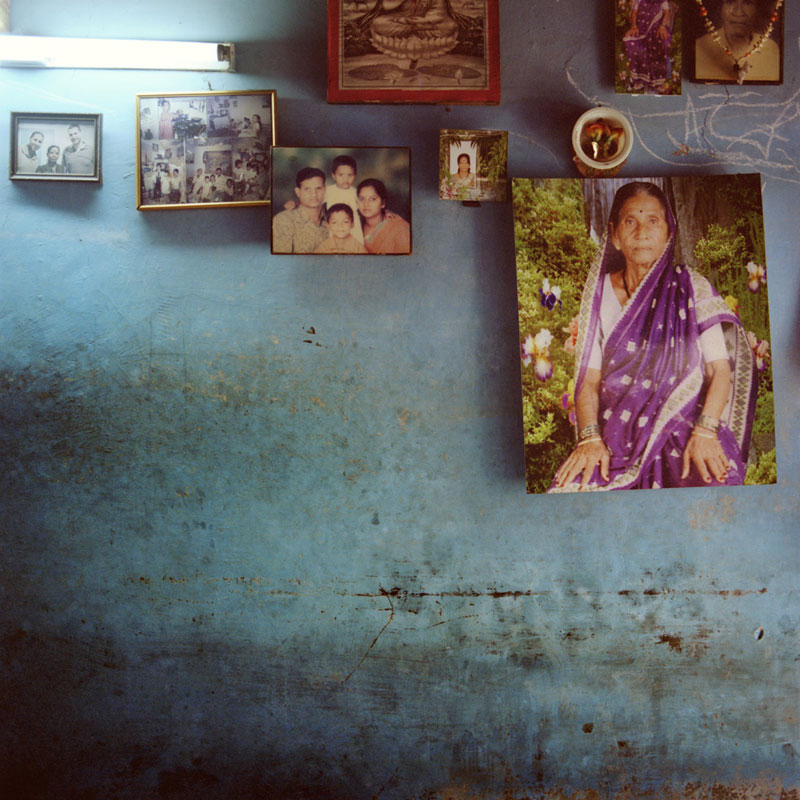 The wall of S.'s house is covered with relatives' photos. On the top left, she also hung a picture of her and the 2 men she carried the baby for, during her first surrogate pregnancy last year. Vithalwadi, September 2012.