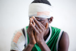 A young man hides his face after recounting the story of his injuries from post-election violence, Bangolo Hospital, western Ivory Coast. He was shot by advancing pro-Ouattara forces and left for dead until a passing soldier heard him groan. Out of bullets, the soldier began hacking at him with a machete.