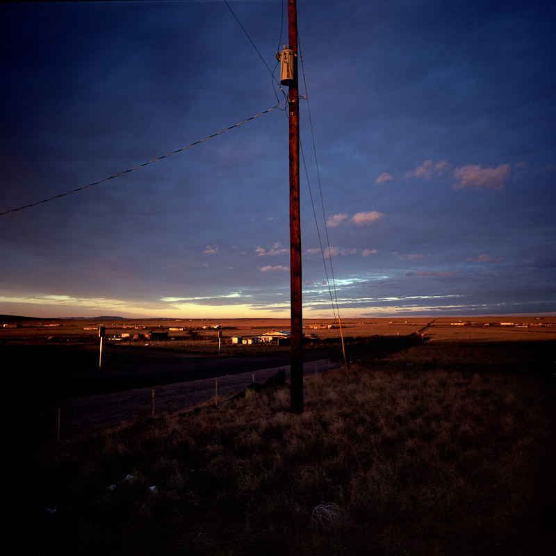 The last power line overlooking the off-the-grid community of Pajarito Mesa, New Mexico. While residents of the Pajarito Mesa legally own their land, a bureaucratic oversight has prevented them from receiving paved roads, running water, and electricity. The lives of people on the Mesa reveal a glance into energy's past and future: while some struggle for the fuel to run their generator for an hour or two each day, their neighbors have been able to afford solar panels, and live comfortably off the grid.