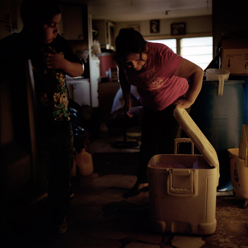 Esperanza Sanchez and her son, Ricardo Alcudia, peer into a cooler that they use for food storage. The family owned a refrigerator but sold it because they needed the money and wanted to reduce their household energy expenses.
