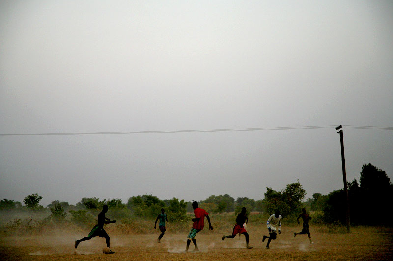 A group of young men plays football in a field in Wantugu. The area lacks vegetation during northern Ghana's long dry season, but it serves as farmland once rains begin to fall.