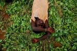 A girl lies in discarded groundnut plants to take a break from harvesting on a farm outside Wantugu.