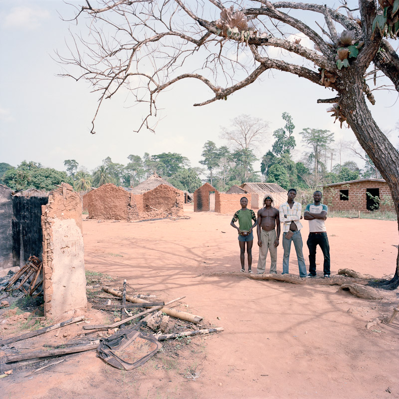 Four local men stand amidst the recent ruins of Zibablu Yeblu, Ivory Coast. While large-scale fighting has ceased in the country, small attacks are still carried out, a sign of continued ethnic strife.