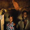 A married couple stand in their recently-rebuilt home in Niambli, Ivory Coast.