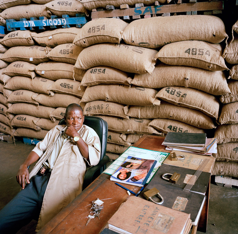 An employee of Saf Cacao, the largest nationally owned cocoa exporter in Ivory Coast, next to stacks of cocoa in San Pedro, Ivory Coast.