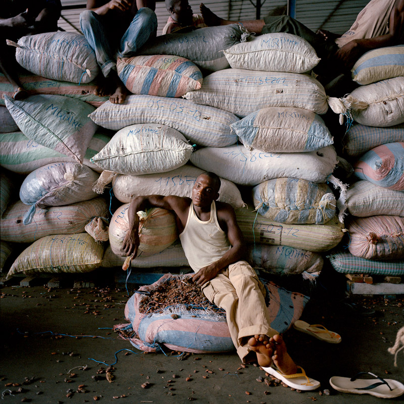 A manual laborer rests amidst sacks of cocoa at Saf Cacao in San Pedro, Ivory Coast.