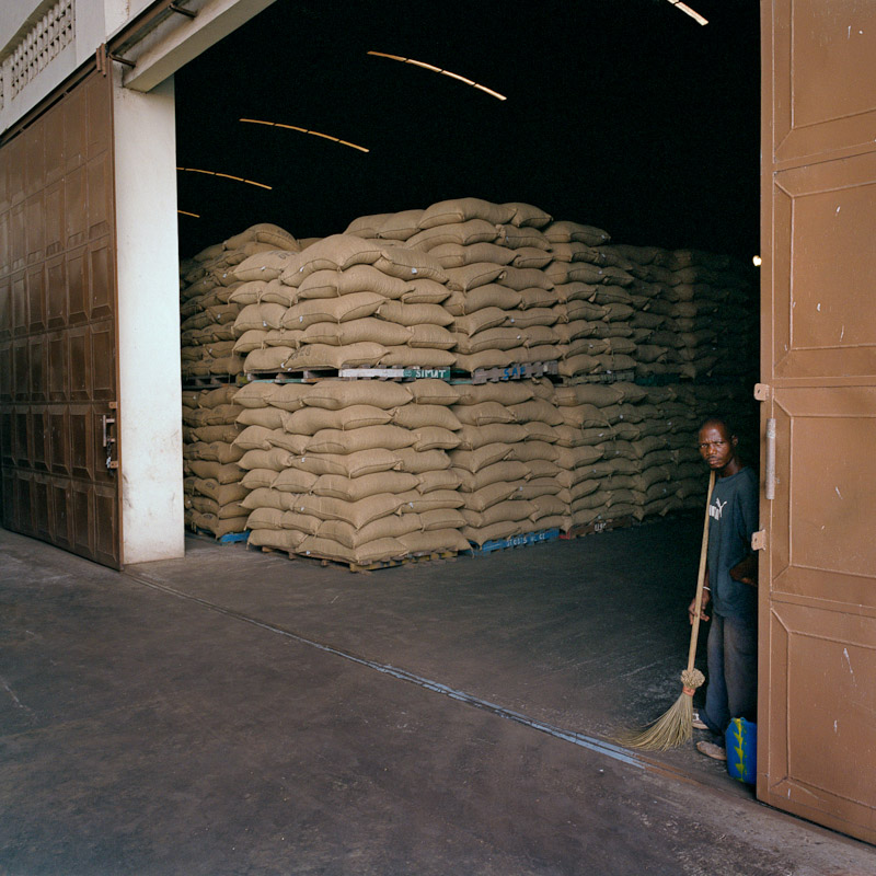 An employee of Saf Cacao next to stacks of cocoa in San Pedro, Ivory Coast.