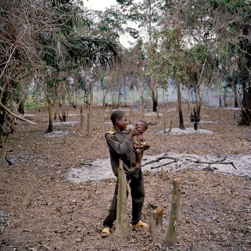 A young farmer holds an infant as the brush around him is burned in preparation for the new planting season on farmland near Pinhou, Ivory Coast.