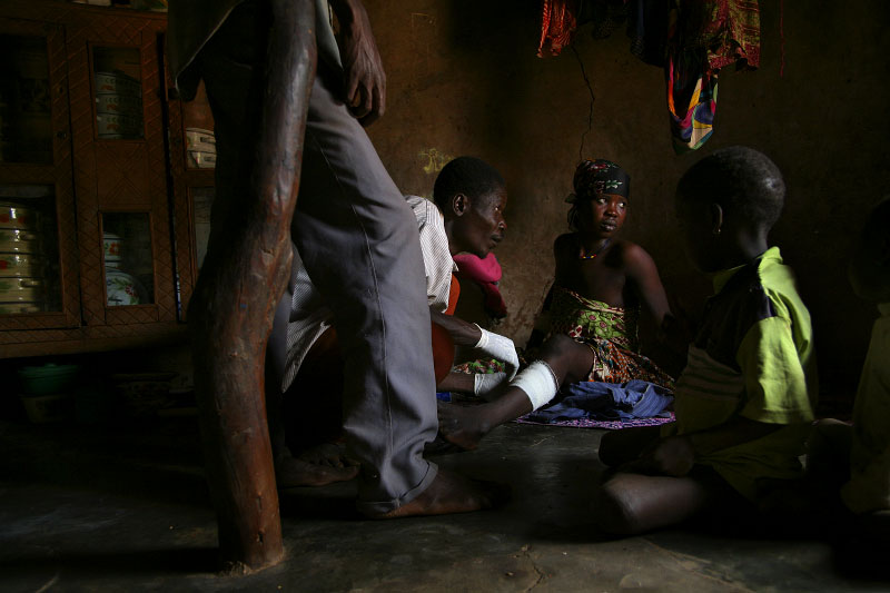 Abukari Memunatu, center, bandages a woman in her home in Kanfehyili, Ghana. Pain in the woman's leg caused by an emerged Guinea worm made it difficult for her to walk, so health workers visited her in her home each day.
