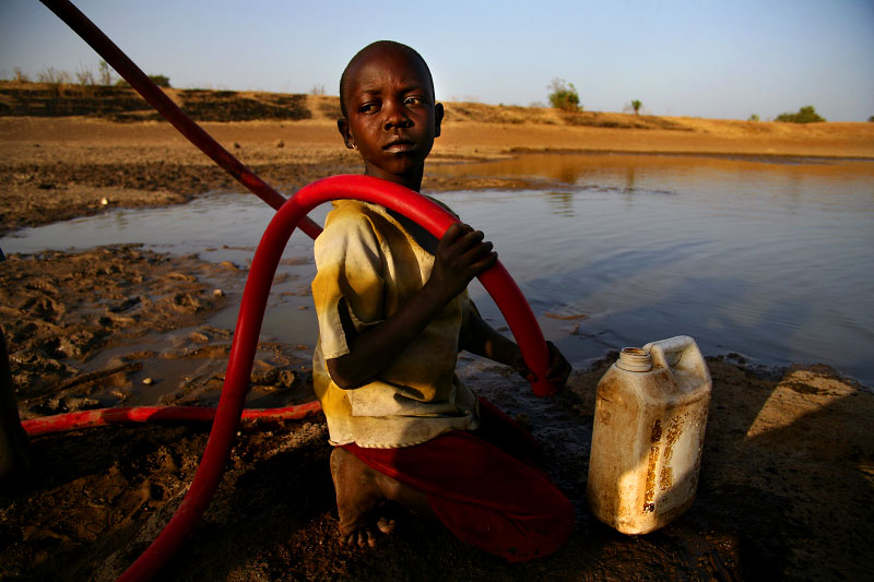 A young girl waits for water to flow from a tube out of Difibihini Dam in Savelugu. In addition to being contaminated with Guinea worm, dam water causes other water-born illnesses. The dam is shared with livestock, including cattle, which wade and defecate in the water.