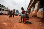 Teenage Kayayo girls rush to their feet to chase after a bus entering Doctor Mensah Market in Kumasi.