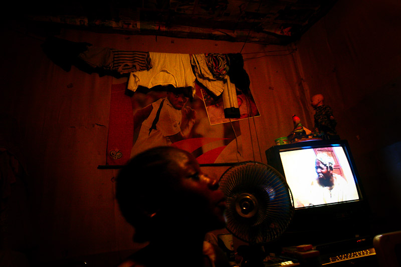 A young woman watches a film in her room in the Accra slum.