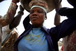 Lamisi lifts a load of yams onto her head in Agbogblushie Market, Accra. {quote}At the end of the day, your whole body will be paining you,{quote} she says of the work.