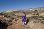 Devastation after the January 12, 2010 earthquake. Bishop Pierre Dumas perform blessings over mass graves in Titanyen. The state left the bodies piled up and the priest brought in bulldozers to give them a proper burial.