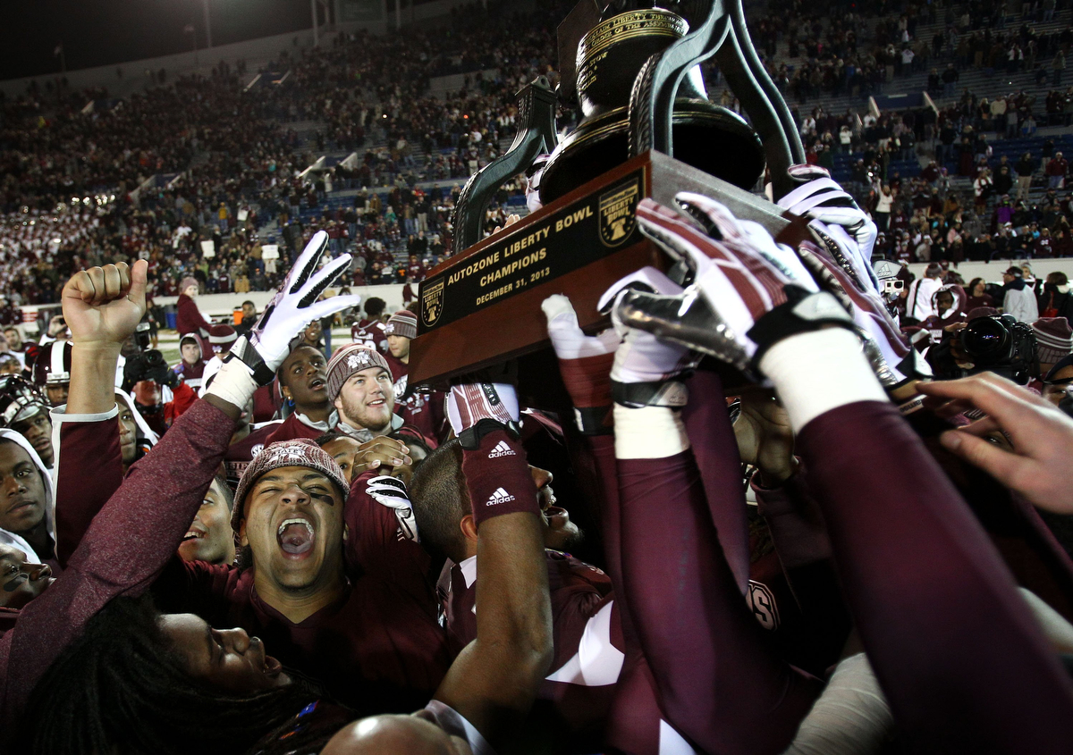 December 31, 2013 - Mississippi State Bulldogs celebrate their 44-7 victory over the Rice Owls as they hoist the 55th annual AutoZone Liberty Bowl trophy. (Mike Brown/The Commercial Appeal)