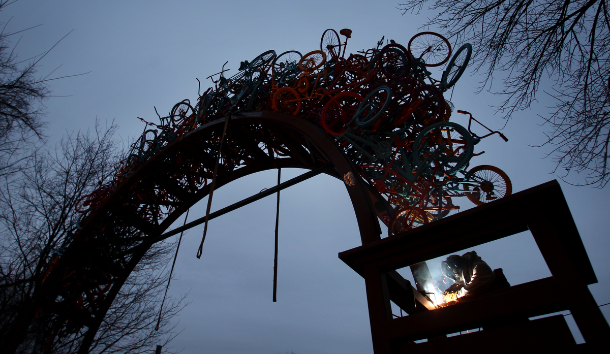 February 12, 2014 - Welder Lorenzo Scruggs works to attach a massive bike covered arch designed by sculptor Tylur French where Sam Cooper dead ends into East Parkway before the sun breaks early Wednesday morning. The sculpture symbolizes a gateway for riders on the Shelby Farms Greeline to enter Overton Park. (Mike Brown/The Commercial Appeal)