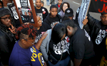 April 14, 2016 - Protesters comfort Diaeatha Cathey (center) as they have a moment of silence and prayer for a fellow protester named Gerial Jeans who was found shot to death in an SUV on April 10. The protesters were gathered with the {quote}Fight for 15{quote} movement seeking higher wages for fast food workers. Jeans participated in past protests. (Mike Brown/The Commercial Appeal)