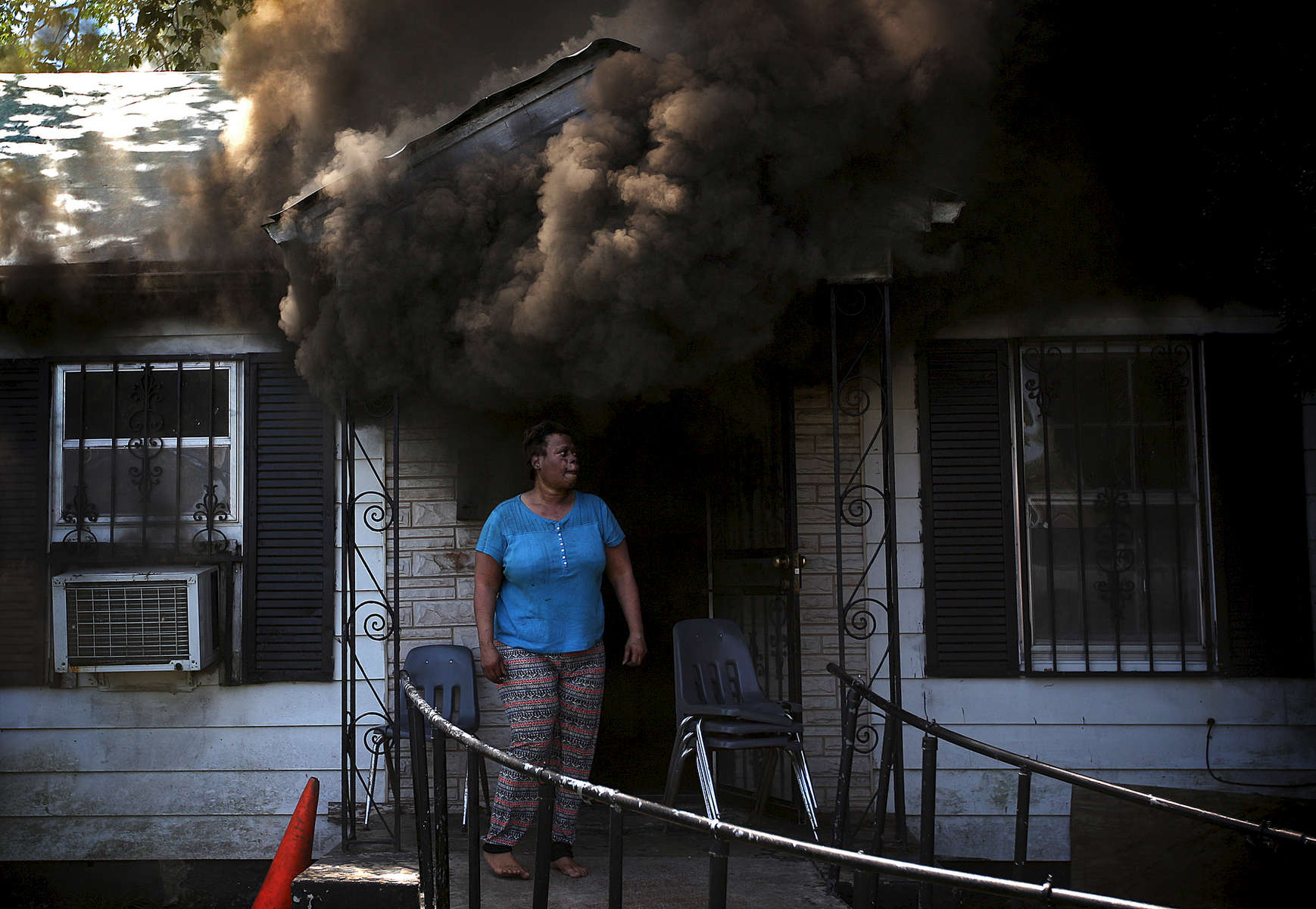 April 24, 2016 - A woman stands of the porch of a home in the 2800 block of Barron in Orange Mound as heavy smoke pours out of the front door and flames were visible in the back of the house while waiting for fire fighters to arrive. The residents, including a man in a wheel chair, escaped the home without injuries. (Mike Brown/The Commercial Appeal)