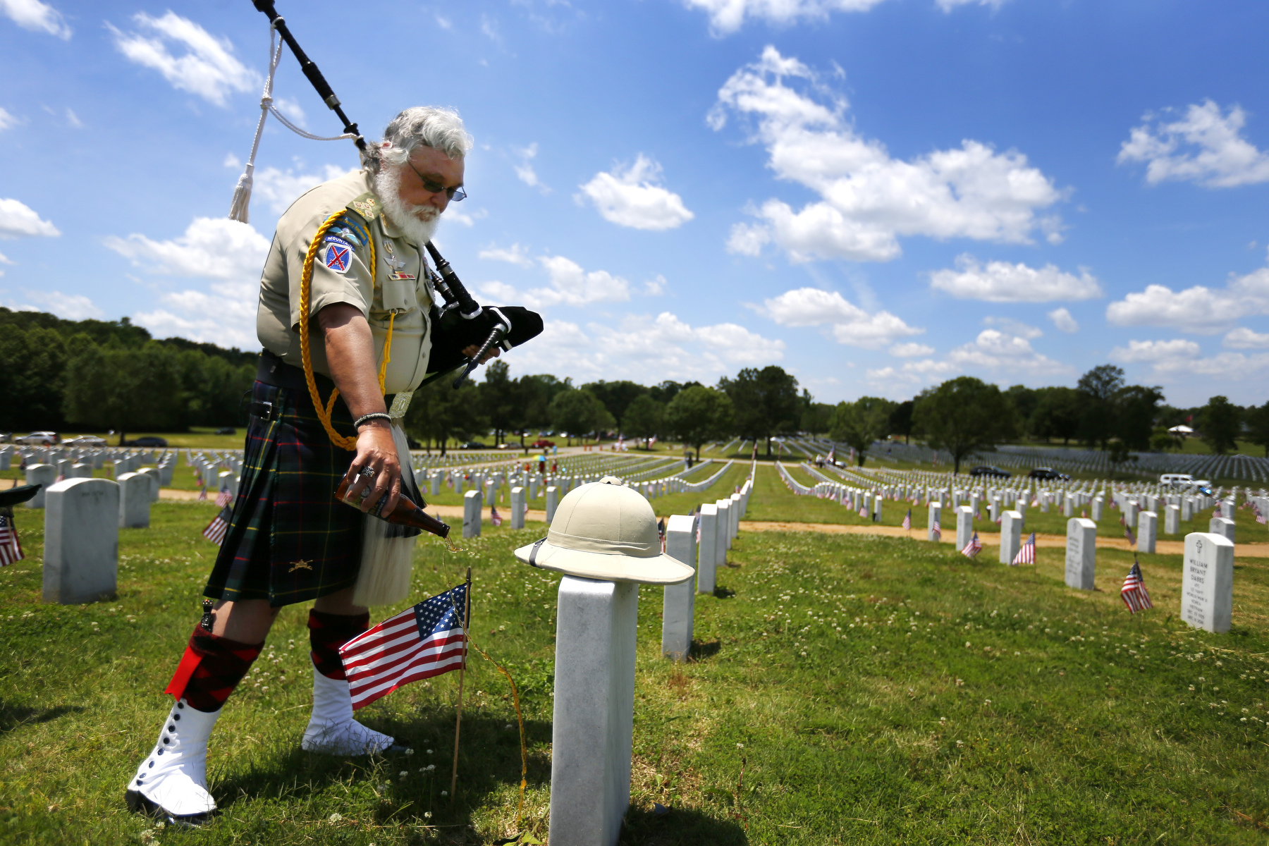 May 30, 2016 - Retired Army Col. Darwin Concon pours out a beer on the grave of his best friend he enlisted into the Army with in August 1978. Concon, who went on to serve a combat tour in Iraq during his 33 year career in the Army, played his bagpipes for his friend, Norman Shannon.  (Mike Brown/The Commercial Appeal)