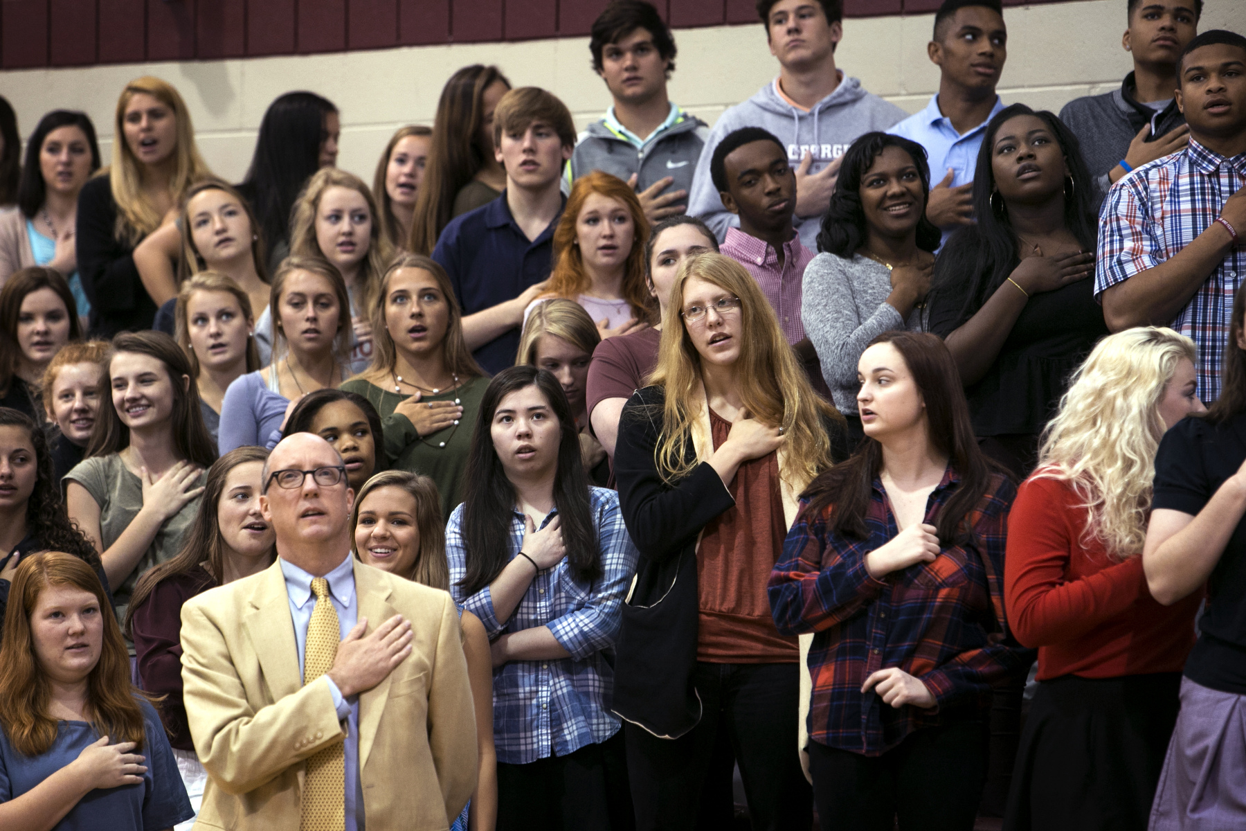 May 9, 2016 - St. George's students, along with head of school J. Ross Peters (bottom, left), say the Pledge of Allegiance before the start of an upper-school chapel service in the school's gym. Later during the service senior Will Courtney stepped to the microphone and took the students and administration to task for what he described as a {quote}noble{quote} experiment that was failing. With only five of the original 19 students who started the first class at the Memphis campus graduating many had been weeded out or left behind, and he noted the visible racial divides in school settings such as the lunchroom and chapel services. {quote}We look for comfort in our groups. I think it's a mistake to place too much value on which groups sit together. People look for shared backgrounds, shared experiences.{quote} Peters later said. (Mike Brown/The Commercial Appeal)