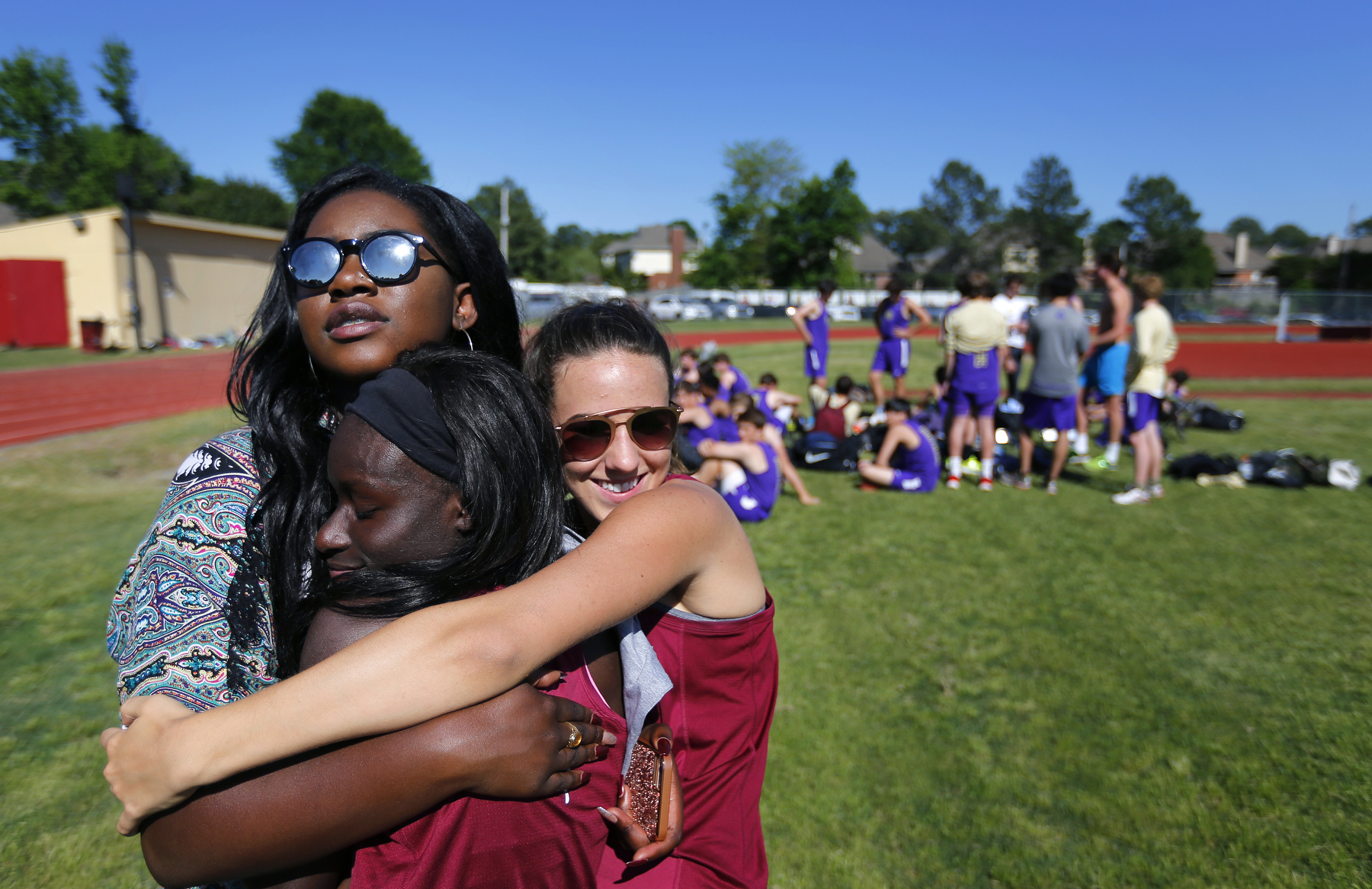 April 27, 2016 - St. George's senior Erica Stevenson (back) and sophomore Whitney Ziegenhorn (right) embrace sophomore Christiana Nyarko during a track meet after school at Evangelical Christian School. {quote}In middle school, I felt like it was a lot easier. The issues we are dealing with now in high school, in general, we didn't notice back then, like race issues.{quote} Stevenson said. {quote}It just became more apparent. The high school years were harder than the middle school years.{quote} (Mike Brown/The Commercial Appeal)