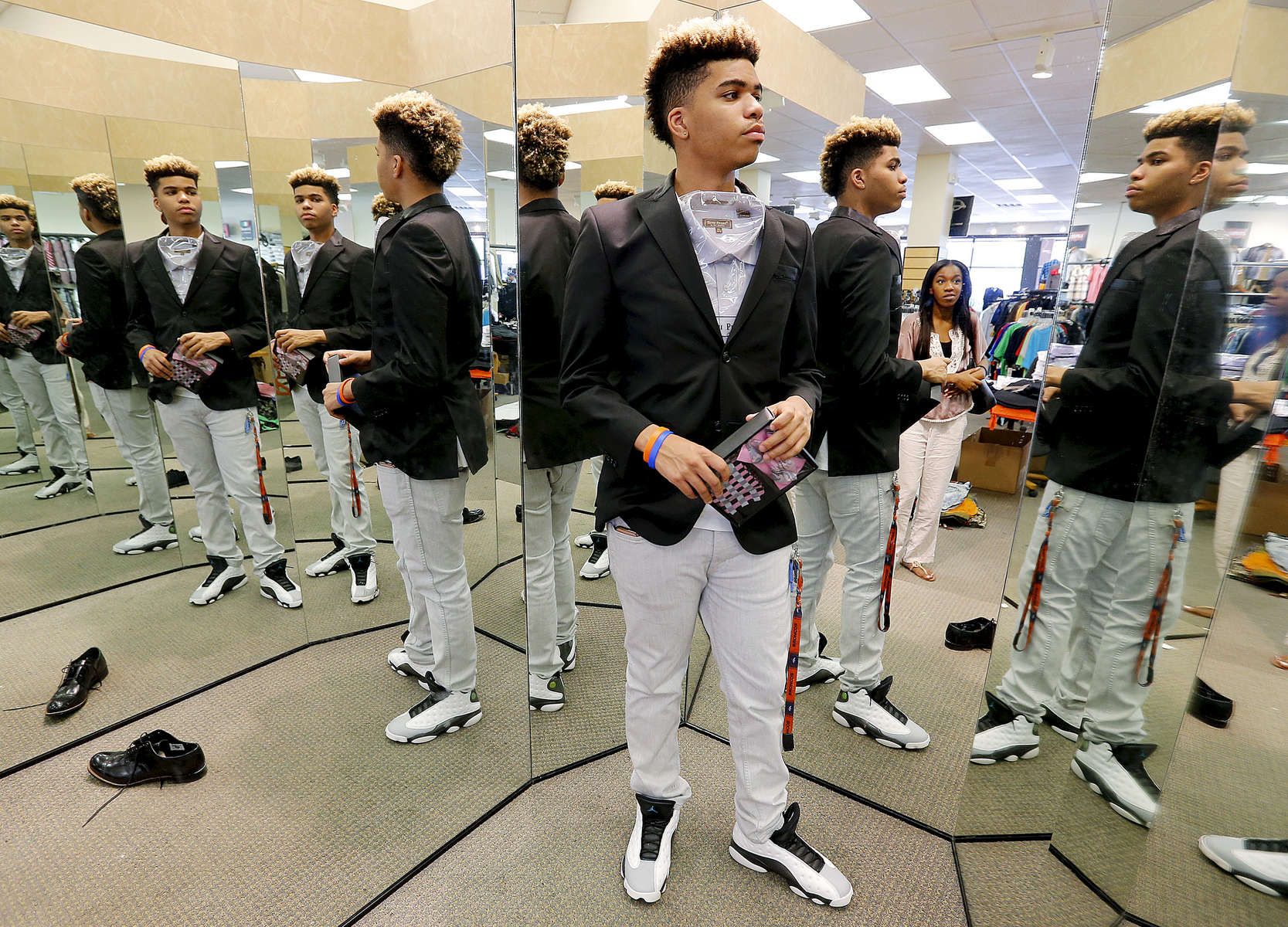 May 3, 2016 - Zearius Jenkins, with help from Paige Madison (reflected in mirror), shops for the perfect shirt to go with the bow tie and handkerchief he purchased to match the dress his date, a former St. George's student, will be wearing for the Southwind High School prom. The core group of original Memphis campus St. George's students have stayed close even though only five of the 19 will be graduating from the school. (Mike Brown/The Commercial Appeal)
